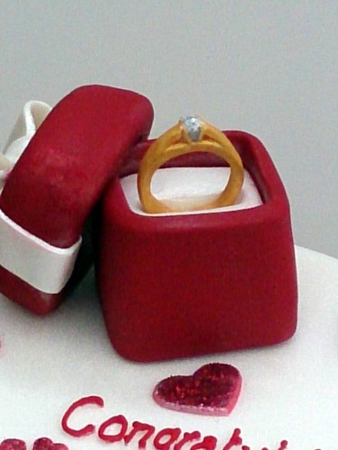 2 tier heart shaped engagement cake with ring in a box