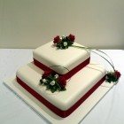 2 tier square stacked wedding cake with deep red rose sugar flower spray