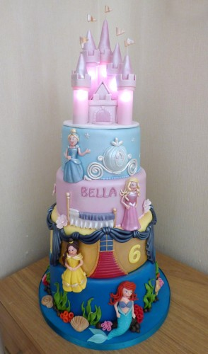4 tier disney princesses birthday cake with an illuminated castle