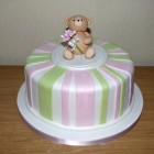 simple striped birthday cake with bear carrying a bouquet of roses