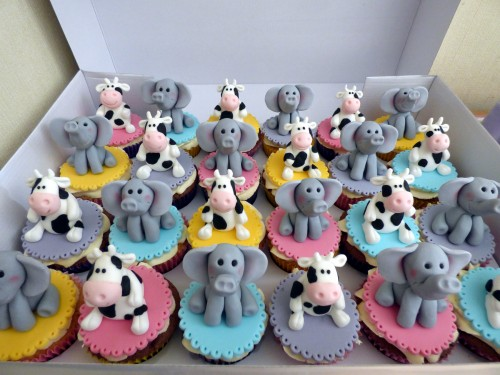 twins 11th birthday cake with cow and elephants and cupcakes